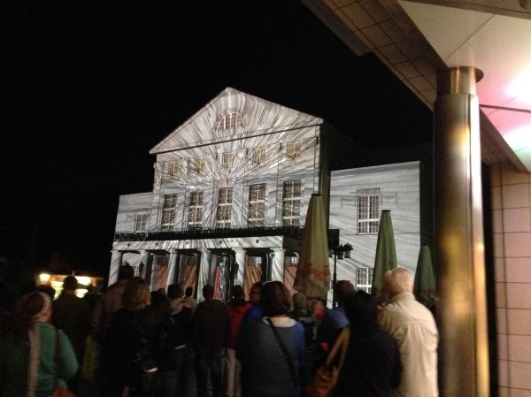 The theatre lit up at night as part of a multimedia presentation that was projected across the Platz onto the facade.